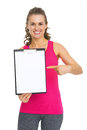 Smiling fitness young woman showing blank clipboard isolated on white Stock Photos