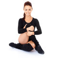 Smiling friendly supple woman with a beautiful smile sitting on the floor with her legs and arms intertwined during training Royalty Free Stock Images