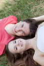Smiling friendly young teenage couple attractive relaxing on a summer day lying head to head on the green grass looking up at the Royalty Free Stock Photos