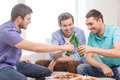 Smiling friends with beer and pizza hanging out Royalty Free Stock Photo