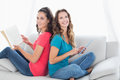 Smiling friends with book and digital tablet sitting at home side view portrait of two young female in the living room Royalty Free Stock Image