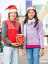 Smiling friends with christmas gift portrait of in courtyard Stock Images