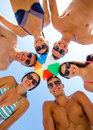 Smiling friends in circle on summer beach friendship happiness vacation holidays and people concept group of wearing swimwear Royalty Free Stock Images