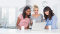 Smiling friends having coffee together and looking at laptop home in kitchen Royalty Free Stock Photo