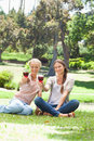 Smiling friends having glasses of red wine in the park Royalty Free Stock Images
