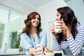 Smiling friends holding coffee mugs at table Royalty Free Stock Photo