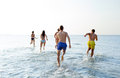 Smiling friends running on beach from back friendship sea summer vacation holidays and people concept group of in swimwear Royalty Free Stock Image