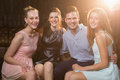 Smiling friends sitting together in sofa at bar Royalty Free Stock Photo