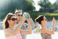 Smiling friends with smartphone taking picture friendship leisure summer technology and people concept group of outdoors Royalty Free Stock Image