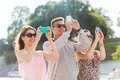 Smiling friends with smartphone taking picture friendship leisure summer technology and people concept group of outdoors Stock Photos