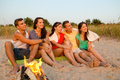 Smiling friends in sunglasses on summer beach friendship happiness vacation holidays and people concept group of sitting near fire Stock Image