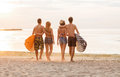 Smiling friends in sunglasses with surfs on beach friendship sea summer vacation water sport and people concept group of wearing Royalty Free Stock Images