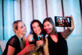 Smiling friends taking a selfie from mobile phone while having wine Royalty Free Stock Photo