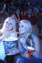 Smiling friends in theatre watching movie female sitting with popcorn and soda Royalty Free Stock Photography