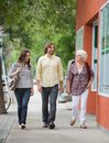 Smiling friends walking on pavement full length of Royalty Free Stock Photo