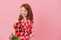 Smiling ginger woman holding bouquet of flowers Royalty Free Stock Photo
