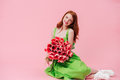 Smiling ginger woman sitting on floor with bouquet of flowers Royalty Free Stock Photo