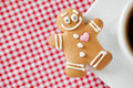 Smiling gingerbread man and coffee cup on table Stock Photography