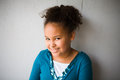Smiling girl african american smiles shyly Royalty Free Stock Photography
