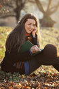 Smiling girl autumn outdoor young beautiful with a book smiles at the camera Royalty Free Stock Photos