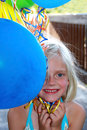 Smiling girl with balloons young blond colorful in hand partially covering face Royalty Free Stock Images