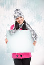 Smiling girl with a blank board and around snowing nice young snow background Stock Images