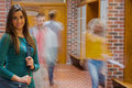 Smiling girl with blurred students walking through corridor portrait of a college Royalty Free Stock Photo