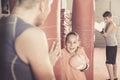 Smiling girl at boxing workout at gym on punching bag