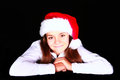 Smiling girl in christmas hat over dark Royalty Free Stock Photography