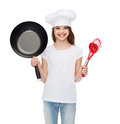 Smiling girl in cook hat with ladle, whisk and pan Royalty Free Stock Photo