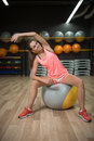 A smiling girl doing fitness exercises. Sports woman stretching on a fit ball on a gym background. Exercising concept. Royalty Free Stock Photo