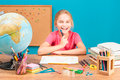 Smiling girl doing her homework young Stock Images