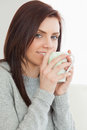 Smiling girl drinking a cup of coffee brunette at home Royalty Free Stock Image