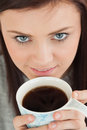 Smiling girl drinking a cup of coffee brunette looking at camera Royalty Free Stock Photo