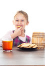 Smiling girl eating cookie with honey on a white background isolated Stock Images