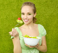 Smiling girl eating salad on green background Royalty Free Stock Photo