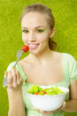 Smiling girl eating salad on green background Royalty Free Stock Photography