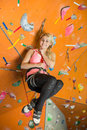 The smiling girl is engaged in rock climbing on gym Royalty Free Stock Photography