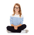 Smiling girl in eyeglasses sitting on floor happiness and people concept Royalty Free Stock Photo