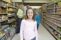 Smiling Girl With Family Shopping In Supermarket
