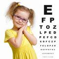 Smiling girl in glasses with eye chart isolated on white Royalty Free Stock Image