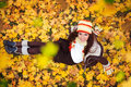 Smiling girl in gold autumn leaves young woman sitting on top view Stock Photo