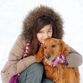 Smiling girl and her dog teenager caucasian in hood hugging outdoors at snow Royalty Free Stock Image