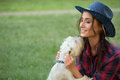 Smiling girl with her small dog cowboy hat and plaid shirt outdoodrs Stock Photos