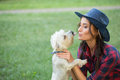 Smiling girl with her small dog cowboy hat and plaid shirt outdoodrs Stock Photography