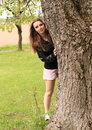 Smiling girl hiding behind tree beautiful woman young trunk of a Royalty Free Stock Photos
