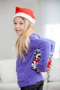 Smiling girl hiding christmas present behind back side view portrait of at home Stock Images