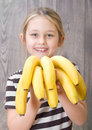 Smiling girl holding a bunch of bananas on the background wooden boards Stock Image
