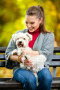 Smiling girl  holding cute maltese dog Royalty Free Stock Photo