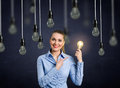 Smiling girl holding a light bulb shining Royalty Free Stock Photo